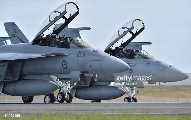 Royal Australian Air Force F18 Hornet pilots wave to the crowd as they taxi down the runway after performing during the Australian International...