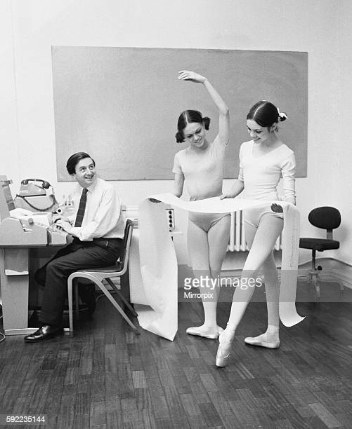 Royal Ballet Company dancers Lesley Collier aged 22 from Orpington and Marilyn Thompson 21 from San Francisco study a print out from a teletype...