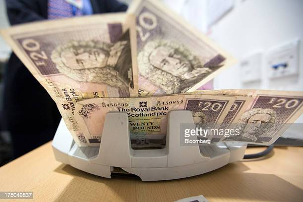 Royal Bank of Scotland Group Plc twenty pound banknotes are displayed in a currency counting machine in this arranged photograph at a Travelex...