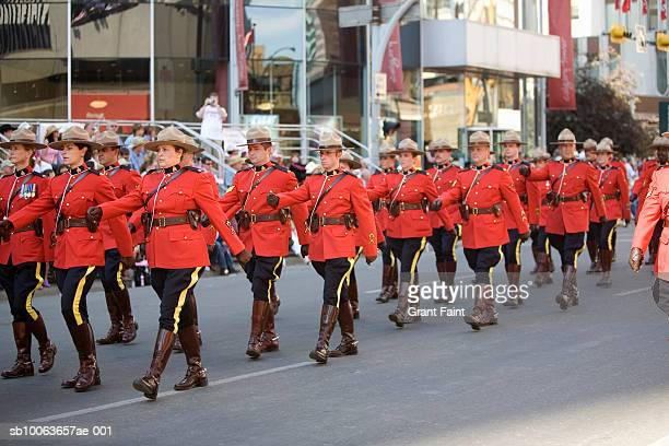 royal canadian mounted police marching calgary stampede parade - calgary stampede stock pictures, royalty-free photos & images