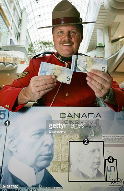 Royal Canadian Mounted Police Sgt Moshe Gordon head of the force's anti counterfeiting force in Ontario holds up the new $5 dollar Canadian bill...