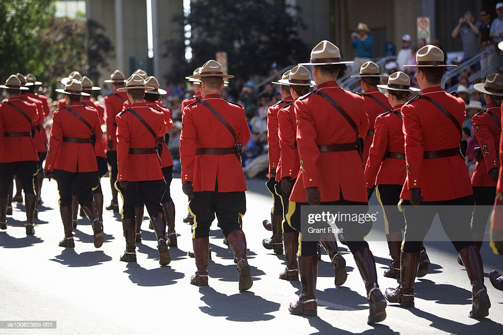 Royal Canadian police in red uniforms marching during parade, rear view : Stock Photo