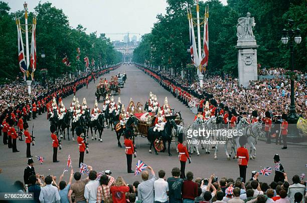 A royal carriage returns Prince Charles and Princess Diana to Buckingham Palace after their wedding Crowds of cheering spectators line the mall as...