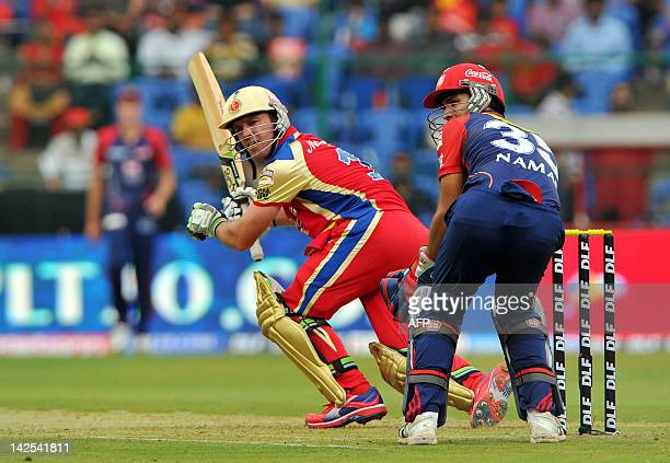 Royal Challengers Bangalore batsman A B DeVilliers is watched by Delhi Daredevils wicketkeeper Naman Ojha as he plays a stroke during the IPL...