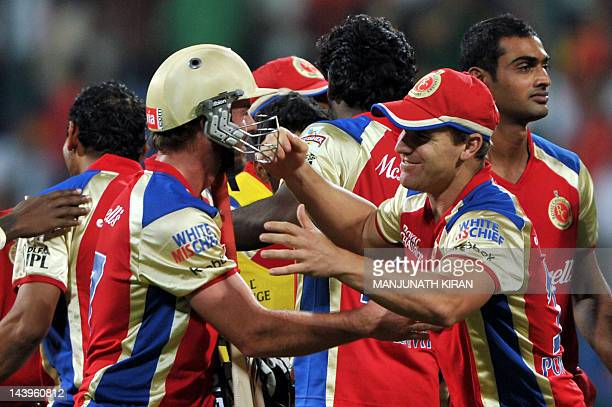 Royal Challengers Bangalore batsman AB DeVilliers is congratulated by his teammates after leading his team to victory during the IPL Twenty20 cricket...
