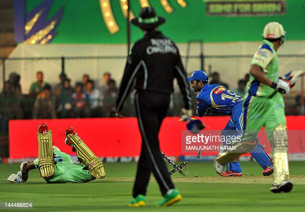 Royal Challengers Bangalore batsman R. Vinay Kumar dives back into the crease as Mumbai Indians wicket keeper Dinesh Karthik stumps the wicket during...