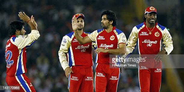 Royal Challengers Bangalore bowler Zaheer Khan celebrating with teammates Chris Gayle and Virat Kohli after the dismissal of Kings XI Punjab batsman...