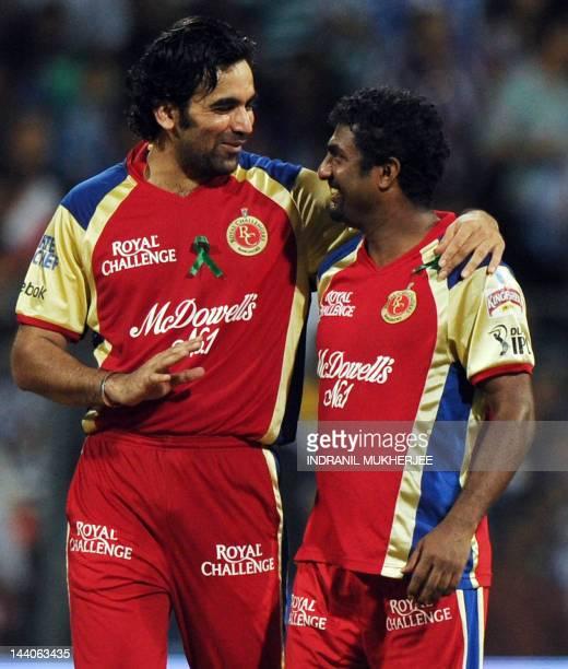 Royal Challengers Bangalore bowlers Zaheer Khan and Muttiah Muralitharan interact after taking the wicket of unseen Mumbai Indians batsman Dwayne...