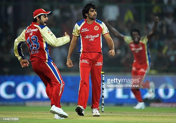 Royal Challengers Bangalore cricketer Zaheer Khan celebrates with teammates after taking the wicket of unseen Delhi Daredevils batsman David Warner...