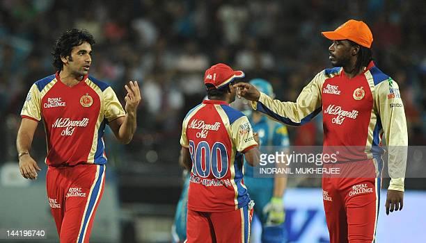 Royal Challengers Bangalore cricketers Zaheer Khan and Chris Gayle interacts as teammate Muttiah Muralitharan walks past during the IPL Twenty20...