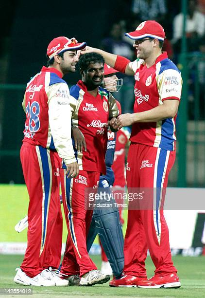 Royal Challengers players Daniel Vettori and Virat Kohli congratulate Muthiah Muralitharan after he took the wicket of Delhi Daredevil player Aaron...