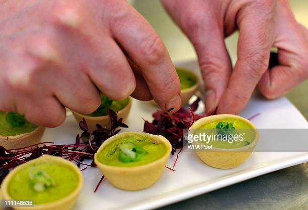 A royal chef adds the finishing garnish to a platter of Wilted Spring Onion and Water Cress quiche canapes food akin to that which is usually served...