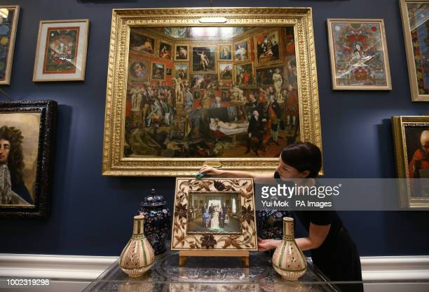 A Royal Collection Trust employee dusting the frame of a photograph of the Royal Family with oil painting The Tribuna of the Uffizi 17727 by Johann...