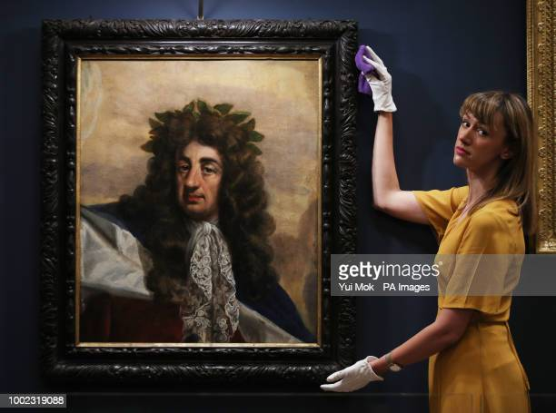 A Royal Collection Trust employee next to a portrait of Charles II by Antonio Verrio during a preview of the Prince amp Patron exhibition in the Ball...