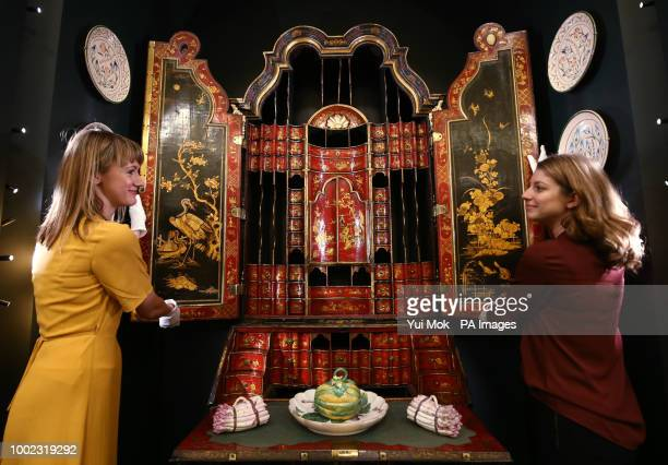 Royal Collection Trust employees pose with a Bureau cabinet c170050 crafted from japanned and gilded wood during a preview of the Prince amp Patron...