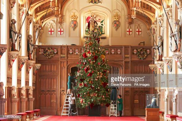 Royal Collection Trust member of staff puts the finishing touches to a 20ft Nordmann fir tree, sourced from the Windsor Great Park, in St George's...