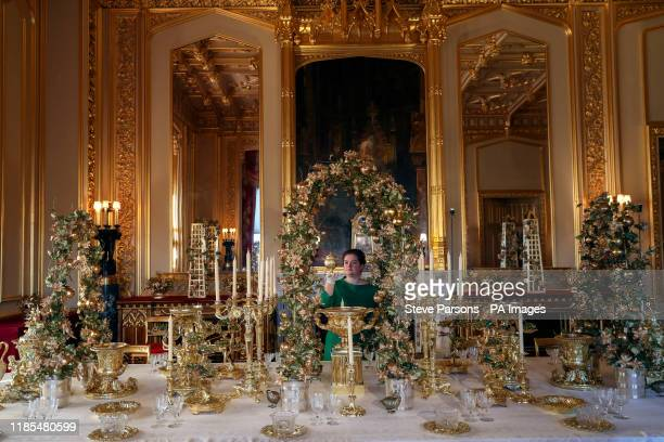 A Royal Collection Trust member of staff puts the finishing touches to the Grand Service in the State Dinning Room at Windsor Castle Berkshire