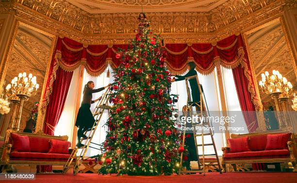 Royal Collection Trust members of staff put the finishing touches to a 15ft Christmas tree in the Crimson Drawing Room at Windsor Castle Berkshire