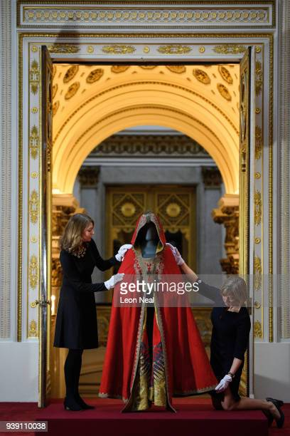 Royal Collection Trust staff pose with the cloak of Napoleon Bonaparte to promote an exhibition to celebrate Prince Charles' 70th birthday and the...