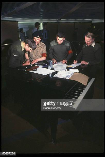 Royal Corps Transport 29 soldiers using grand piano for work table before leaving for Falklands on QE2