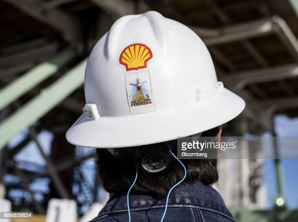 Royal Dutch Shell Plc representative wears a hard hat with a Permian Basin sticker while on an oil rig site near Mentone Texas US on Thursday March 2...