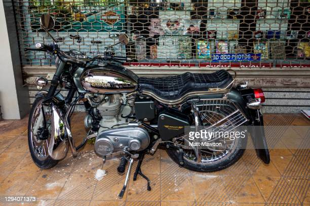 a royal enfield bullet motorcyle on the streets of mumbai india - indian royal enfield stock pictures, royalty-free photos & images