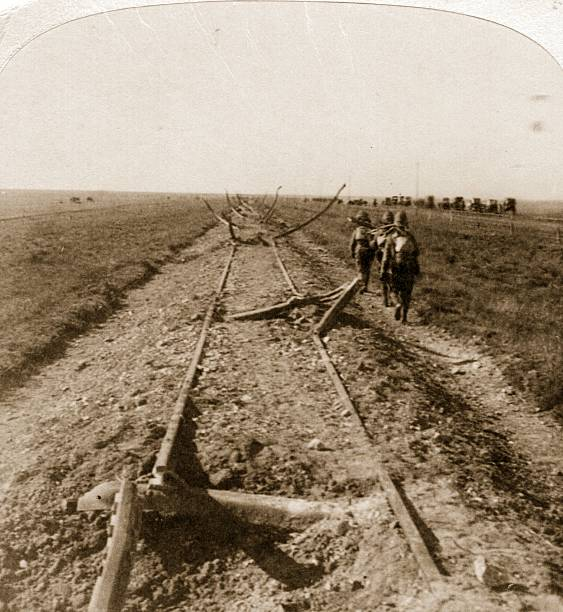 Royal Engineers walk along a railway damaged by the...