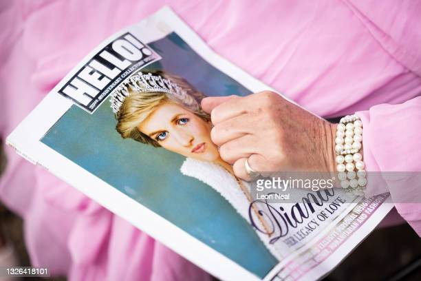 Royal fan Anne Daley holds a copy of Hello magazine on what would have been the 60th birthday of Princess Diana, at Kensington Palace on July 01,...