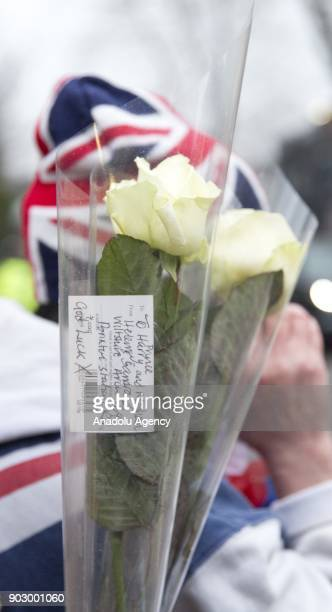 Royal fan holds a flower bouquet as Prince Harry and his fiance Meghan Markle arrive to Pop Brixton to see the broadcaster's work supporting young...