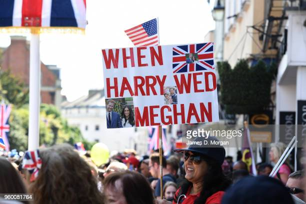 Royal fan holds a sign before the Duke and Duchess of Sussex left in the Ascot Landau carriage during the procession after getting married at St...