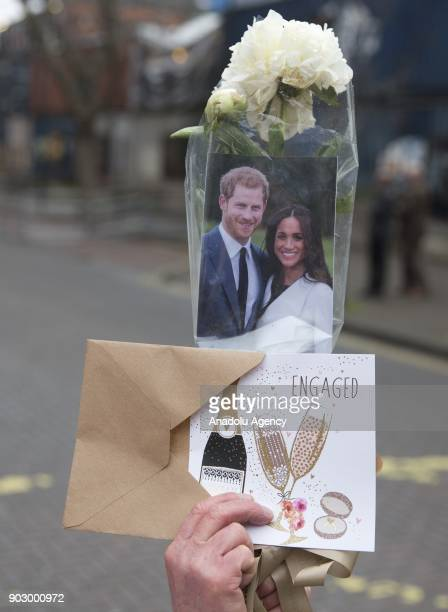 Royal fan holds an engagement card of Prince Harry and his fiance Meghan Markle as they arrive to Pop Brixton to see the broadcaster's work...