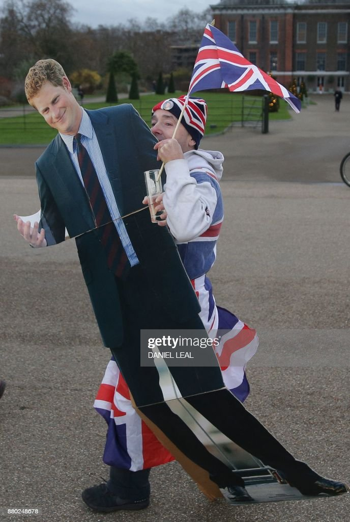 Royal fan John Loughry carries a cardboard cut-out of Britain's Prince Harry, at Kensington Palace in west London on November 27, 2017, after Harry posed with his fiancée US actress Meghan Markle. Britain's Prince Harry will marry his US actress girlfriend Meghan Markle early next year after the couple became engaged earlier this month, Clarence House announced on Monday. / AFP PHOTO / Daniel LEAL