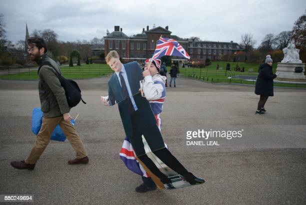 Royal fan John Loughry carries a cardboard cutout of Britain's Prince Harry at Kensington Palace in west London on November 27 after Harry posed with...