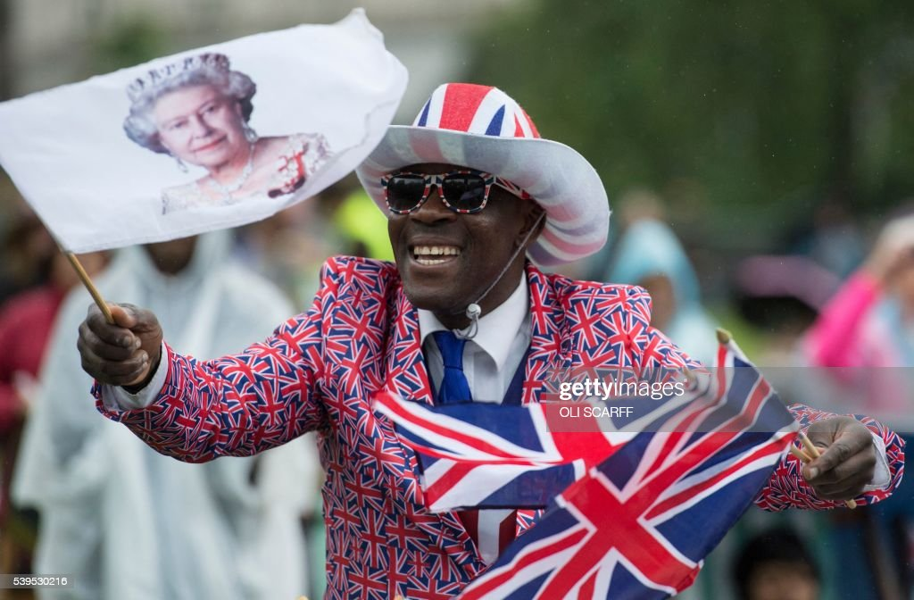 Royal fan Joseph Afrane waves a flag as he watches events on a large screen in Green Park, as hundred's of guests from organisations with which the queen has links gather for the Patron's Lunch, a special street party outside Buckingham Palace in London on June 12, 2016, as part of the three day celebrations for Queen Elizabeth II's official 90th birthday. Up to 10,000 people are expected to attend the Patron's Lunch along with the monarch, her husband Prince Philip, Prince William and Prince Harry. SCARFF