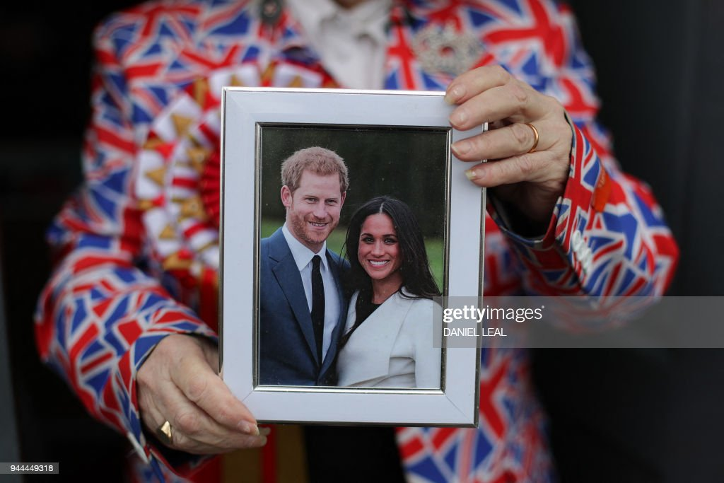Royal fan Margaret Tyler poses for a photograph holding a framed picture of Britain's Prince Harry and his fiancee Meghan Markle, outside her house in north London on April 4, 2018. Festooned with bunting and guarded by a stained-glass sentry, the eccentric London home of retired charity worker Margaret Tyler is already bursting with souvenirs, but is getting fuller by the day ahead of a busy summer for royal fans. The 'loyalist royalist' has been collecting souvenirs for four decades, amassing over 10,000 mugs, life-size cutouts, effigies, tapestries, books, posters, toilet seats, nodding corgis, tea-sets, and countless other nick-nacks in her London home. / AFP PHOTO / Daniel LEAL-OLIVAS / TO GO WITH AFP STORY by James PHEBY