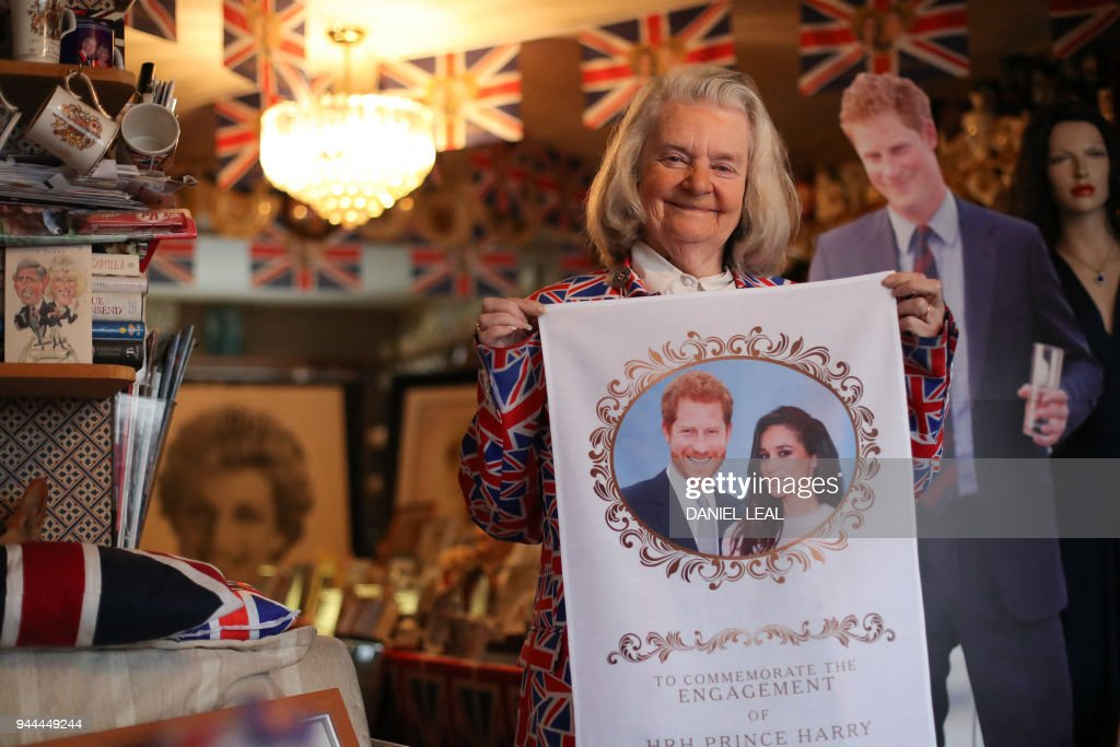 Royal fan Margaret Tyler poses for photographs while holding memorabilia celebrating the forthcoming wedding of Britain's Prince Harry to his fiancee Meghan Markle, in her home in north London on April 4, 2018. Festooned with bunting and guarded by a stained-glass sentry, the eccentric London home of retired charity worker Margaret Tyler is already bursting with souvenirs, but is getting fuller by the day ahead of a busy summer for royal fans. The 'loyalist royalist' has been collecting souvenirs for four decades, amassing over 10,000 mugs, life-size cutouts, effigies, tapestries, books, posters, toilet seats, nodding corgis, tea-sets, and countless other nick-nacks in her London home. / AFP PHOTO / Daniel LEAL-OLIVAS / TO GO WITH AFP STORY by James PHEBY