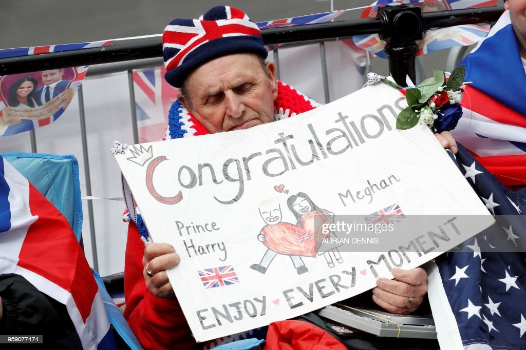 Royal fan Terry Hutt holds a placard as he sits on a street corner along the Wedding procession route to secure his viewing spots for the Wedding day, near Windsor Castle in Windsor, west of London on May 16, 2018, as preparations continue ahead of the forthcoming Royal wedding. - Britain's Prince Harry and US actress Meghan Markle will marry on May 19 at St George's Chapel in Windsor Castle.