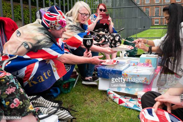 Royal fans eat birthday cake as they prepare to watch a live broadcast of the unveiling of a statue on what would have been the 60th birthday of...