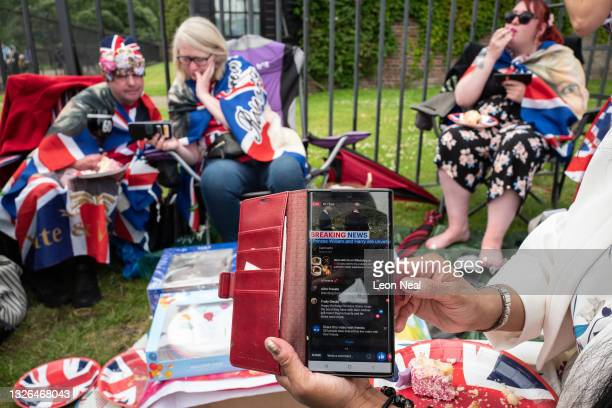 Royal fans gather to watch a live broadcast of the unveiling of a statue on what would have been the 60th birthday of Princess Diana, at Kensington...