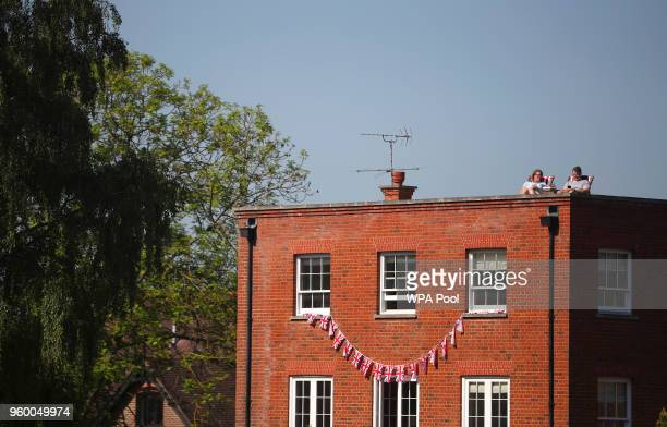 Royal fans sit on the building's rooftop ahead of wedding of Britain's Prince Harry to Meghan Markle in Windsor on May 19 2018 in Windsor England