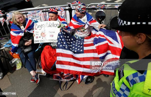 Royal fans Terry Hutt and John Loughrey adorned in Union and US flags sit on a street corner along the Wedding procession route to secure their...