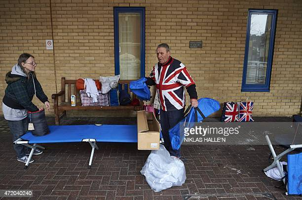 Royal fans Terry Hutt Jacquie Knighton pack their belongings after camping outside the Lindo Wing at St Mary's Hospital in London on May 3 2015 to...