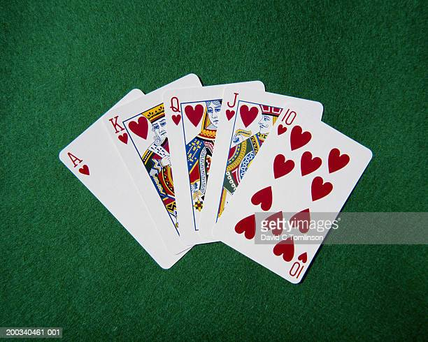 royal flush hand of cards, hearts suit, on playing baize, close-up - ポーカー ストックフォトと画像