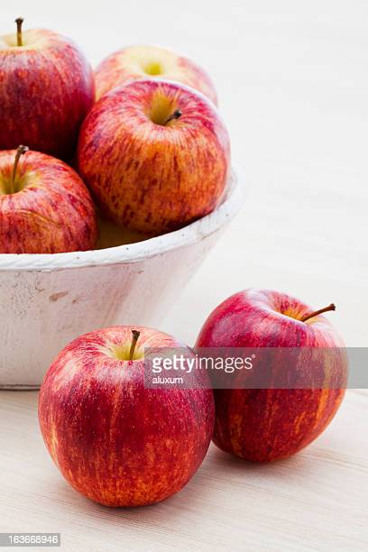 royal gala apples in a bowl and on the table  - royal gala apple stock photos and pictures