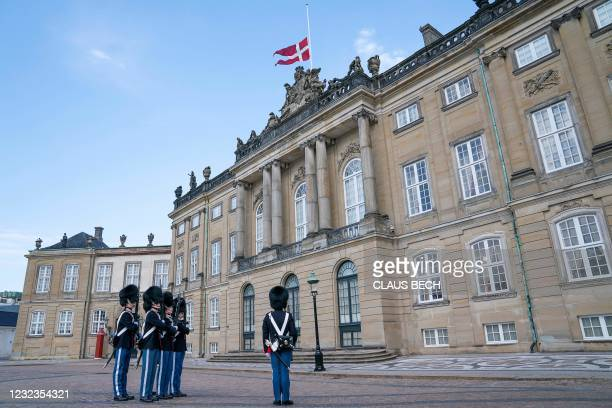 Royal guards stand to attention as the Danish national flag flies at half mast at Amalienborg Palace in Copenhagen on April 17 on the occasion of the...