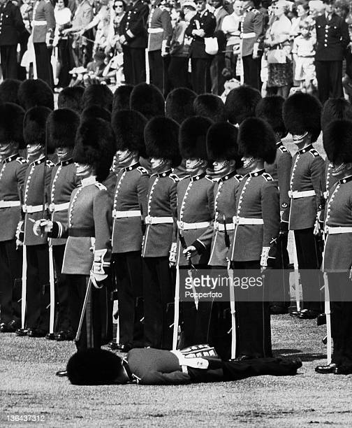 A Royal Guardsman passes out during a heat wave in London on 1st June 1963