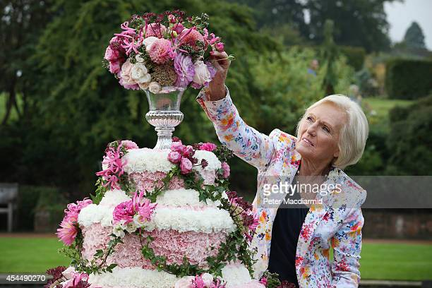 Royal Horticultural Society Ambassador and cook Mary Berry adds a flower to a floral cake at the opening of the RHS Flower Show at Wisley Gardens on...