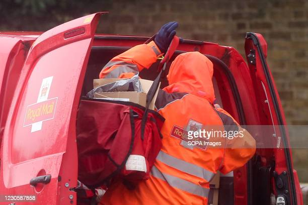 Royal Mail postal worker preparers to deliver the mail at his van in London. According to Royal Mail, some areas of London have seen a reduced...