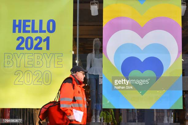 Royal mail postman delivers post as he walks past a 'Hello 2021, Bye 2020' sign on January 05, 2021 in Birmingham, England. British Prime Minister...