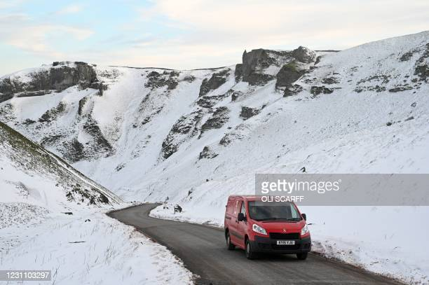 Royal Mail van is driven along Winnats Pass through snow-covered countryside near Castleton in The Peak District in northern England on February 11...